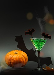 Green cocktail for a Halloween party with decorative bats and pumpkins. On a black background with smoke and light spots