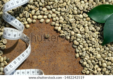 Green coffee bean raw  and   tape measure with centimeter on rustic iron background. Consept of reducing aids