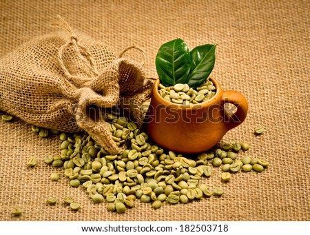 Green coffee beans and clay cup on sacking