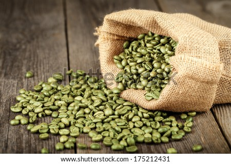 Green coffee beans in coffee bag made from burlap on wooden surface. Focused in middle of the frame.