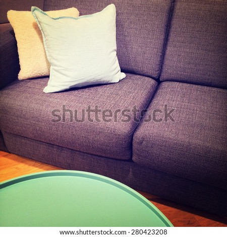 Green coffee table and sofa with cushions. Modern furniture.