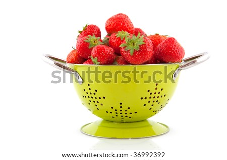 Green colander with strawberries isolated over white
