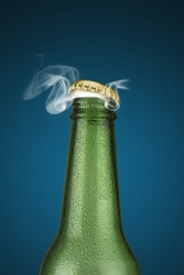 Green cold beer bottle with water drops and golden cap open on blue background
