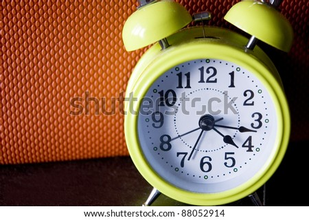 green color alarm clock with orange color background