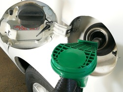 green color fueling pump nozzle filling up a vehicle petrol tank with unleaded fuel.