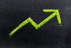 Green color hand drawing chalk in arrow up shape on black board background (Concept of revenue increase, stock or business growth)