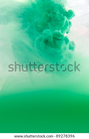 Green Color pigments dissolved in acrylic paint floating into water.