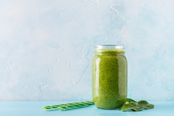 Green-colored smoothies / juice in a jar on a blue background.