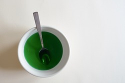 Green colored water in bowl for eggs dying for easter, with a spoon. Simple, from above / flat lay with bold colors and white background, space for text / copy.