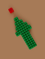 green computer cursor or directional arrow made of blocksand building parts on a neutral beige background