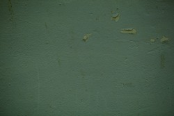 Green concrete wall background texture with flaky paint and stippled surface with side vignettes in a full frame view