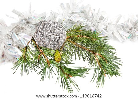 Green conifer branch with silver ball and tinsel isolated on white