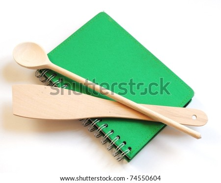 green cookbook and kitchenware isolated on white background