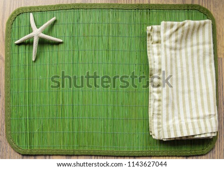 Green cotton napkin on a green bamboo placemat with a white sea star in the corner