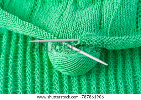 Green cotton yarn with knitting needles and a tangle of yarn (background, concept) #787861906