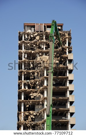 Green crane demolishing a highrise building