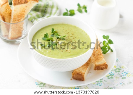 Photo of  Green cream vegetable soup broccoli, peas, zucchini, spinach) with toast, croutons. Delicious vegetarian healthy spring, summer food on light background