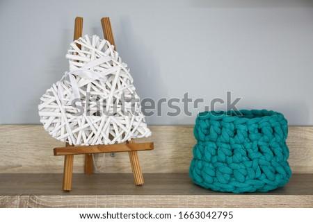 Green crochet basket and a wicker heart on a light wooden shelf against a gray wall Stock fotó ©