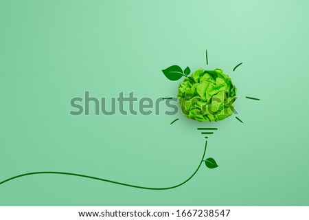 Green crumpled paper light bulb on green background, Corporate Social Responsibility (CSR), eco-friendly business and environmental concepts, copy space