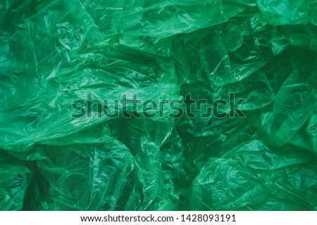 Green crumpled plastic bag texture background. Waste recycle concept. Polyethylene clear garbage bags.  #1428093191