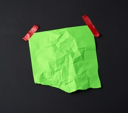 green crumpled sheet of paper glued with rubber red adhesive tape on a black background, copy space