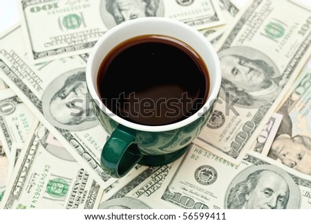 Green cup of coffee on money isolated on white