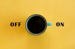 Green cup with black coffee on yellow background switching on. On and off signs, on and off switch. Concept of good morning, waking up, coffee break and caffeine. Creative coffee related idea.