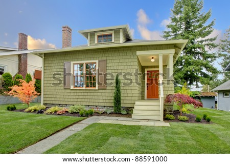 Green cute small craftsman house with orange door