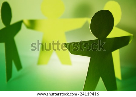 green cutouts holding hands - stock photo