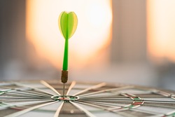Green dart arrow hitting in the target center of dartboard using as background target business , achieve and victory concept .