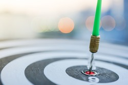 Green dart arrow hitting in the target center of dartboard with modern city and sunset background. Successful Target business, achieve plan and victory winner concept