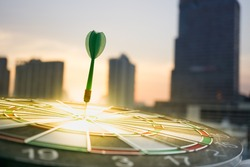 Green dart arrow hitting in the target center of dartboard with modern city and sunset background. Target business, achieve and victory concept .