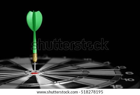 Green dart hitting the center of target. Dartboard with dart arrow hitting the center.