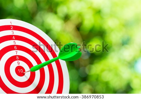 Green darts arrows in the target center on green bokeh background. Success hitting target aim goal achievement concept background. close up. ストックフォト ©