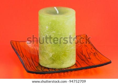 Green decorative candle isolated on orange background