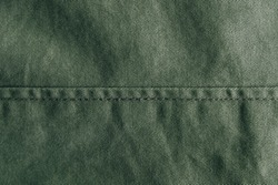 Green denim background decorated with a seam. Green denim seam texture. Top view. Copy, empty space for text