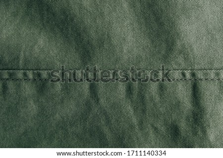 Green denim background decorated with a seam. Green denim seam texture. Top view. Copy, empty space for text Сток-фото ©