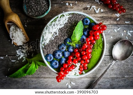 Green detox smoothie with berries on wooden background bowl