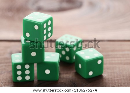Green dice on brown wooden table #1186275274