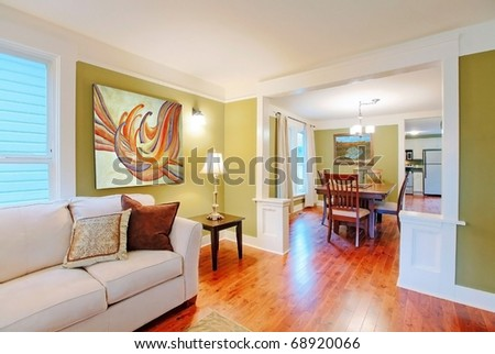 Green dining and living room with nice furniture and art.