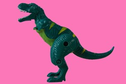 Green Dinosaur, Plastic Toy Animal isolated on pink background.