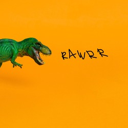 green dinosaur with open mouth and inscription rawrr on bright orange background