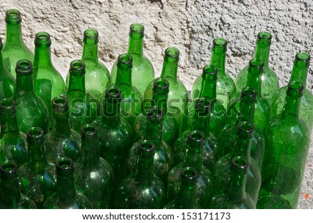 Green dirty empty wine bottles close-up