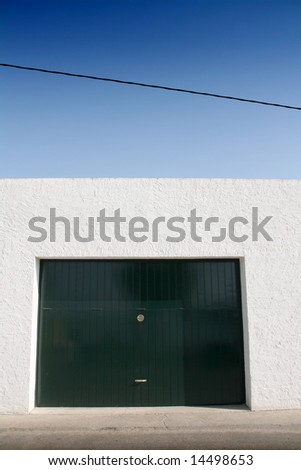 green door garage, white wall and blue sky, sidewalk and street