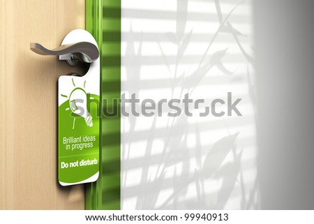 green door hanger onto a handler with room for text on the wall at the right side. On the sign it's written brilliant ideas in progress, do not disturb