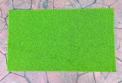 Green door mat on cement floor
