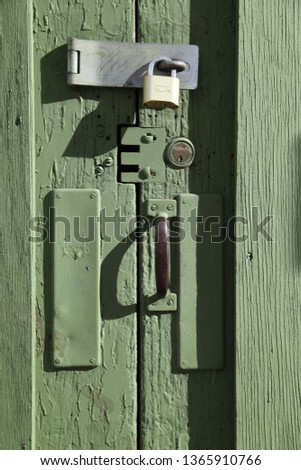 Green door on a Victorian-era building with a modern steel hasp and a bass lock.