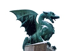 Green dragon statue from a Dragon bridge in the capital city of Slovenia Ljubljana isolated on white background during snow.