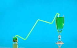 Green drinking straw shaped like a line of a growing graph, connecting two glasses filled with green liquid. Growth, investment and trading concepts.