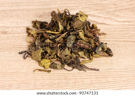 Green dry tea on wooden table